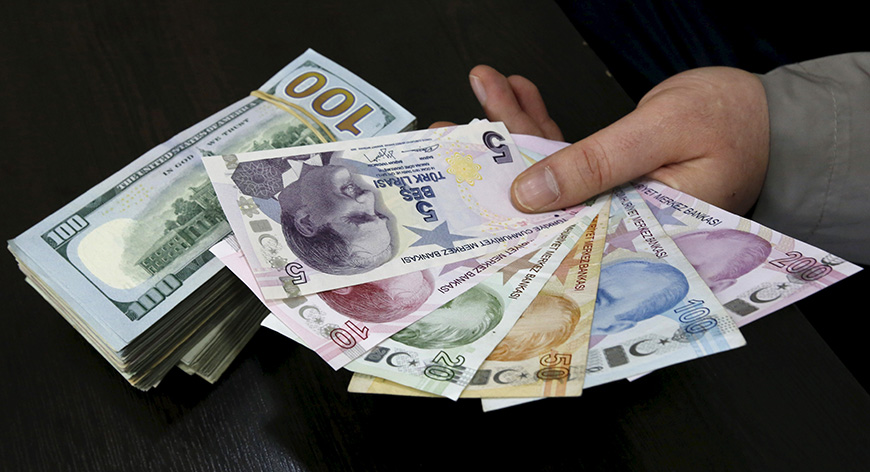 A money changer holds Turkish lira banknotes next to U.S. dollar bills at a currency exchange office in central Istanbul April 15, 2015.